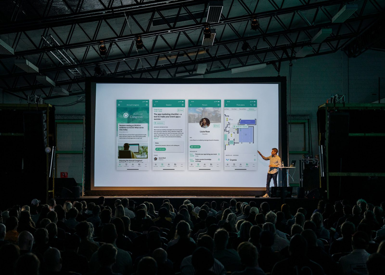 person giving a presentation showing four app screens to a large crowd